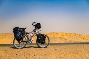 Cycling in Sahara from Dongola to Karima in Sudan against strong winds,